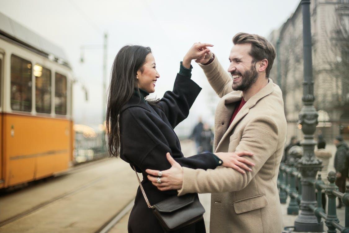 Happy couple dancing on sidewalk